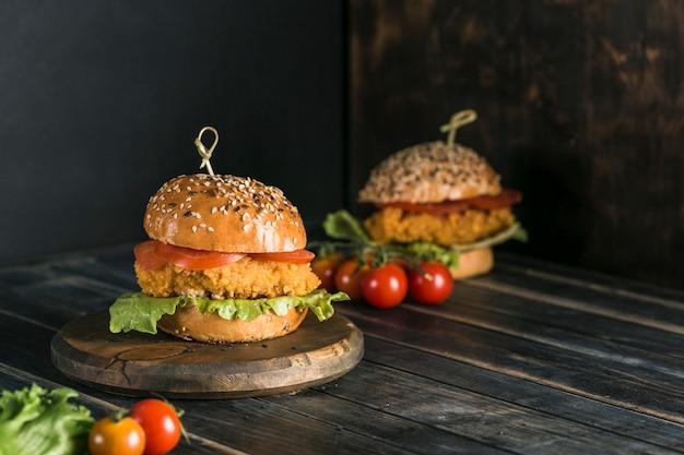 Классический бургер с курицей в булочке с кунжутными помидорами, листьями салата и горчичным соусом.
