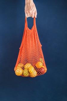 人間の手のオレンジ色のひも袋にリンゴとレモン