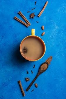 Популярный азиатский согревающий напиток масала чай в желтом с кориандром, деревянной ложкой с корицей и стеблем розы на классическом синем фоне.