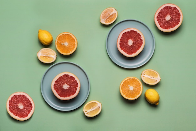 Апельсины, лимоны и грейпфруты на плоской тарелке на цветном светло-зеленом фоне. концепция здорового питания и витаминов.