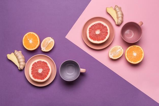 Лимоны, апельсины, грейпфрут и имбирь на плоской тарелке на фиолетово-розовом цветном фоне. концепция здорового питания и витаминов.