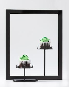 Кексы с зеленым кремом на черной рамке