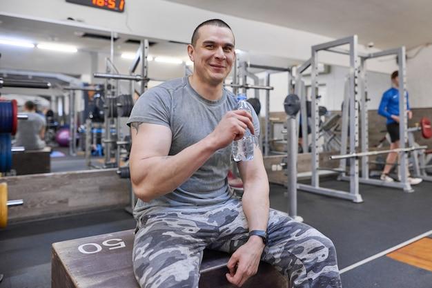 ジムでボトルから水を飲む若い筋肉の強い男。