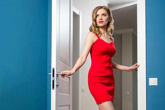 赤いドレスのファッショナブルな女の子がインテリアのドアを開きます