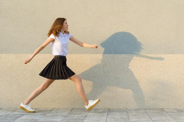 若い女の子は灰色の壁に沿って歩く