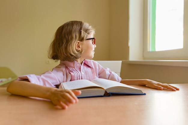 Утомленная маленькая студентка смотрит в окно, сидя за столом с большой книгой