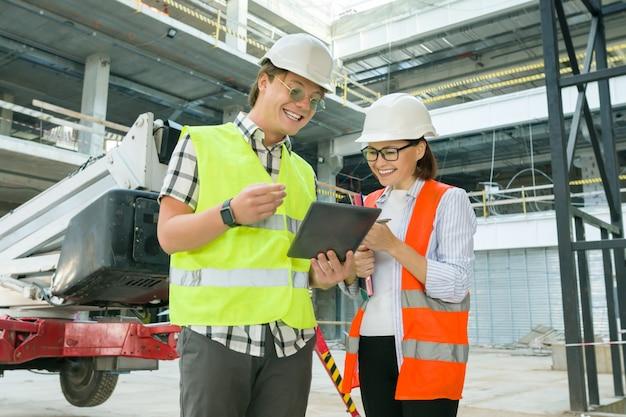 Женщина архитектор и мужчина строитель на строительной площадке