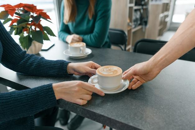 喫茶店の冬の季節。一杯のアートコーヒーと男バリスタのクローズアップ手