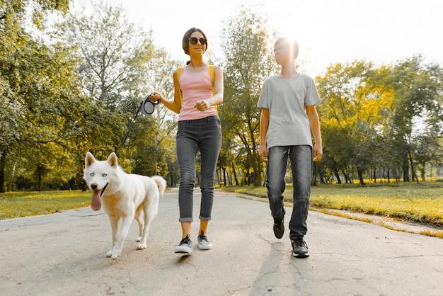 Дети подростки мальчик и девочка гуляют с белой собакой хаски