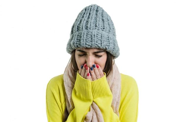 女性は暖かい帽子とスカーフで風邪をひいた