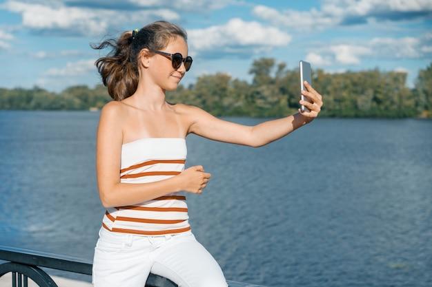 若い女の子ブロガーは彼のブログのために写真やビデオを撮ります。夏都市公園の路上で笑っている女の子。