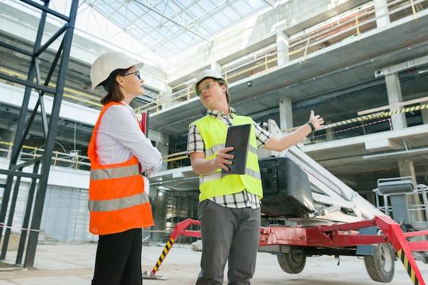 Мужчина инженер и женщина архитектор на строительной площадке