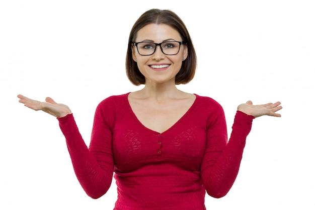メガネと成熟した笑顔の女性の肖像画は彼女の手を上げて、彼女の手のひらの上で何かを見せて