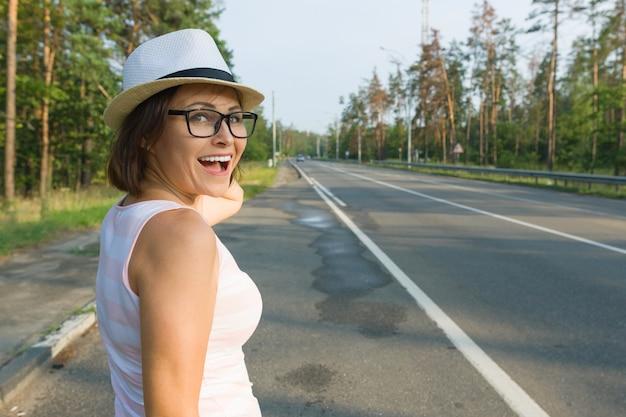 帽子の中年の笑顔の女性の屋外のポートレート
