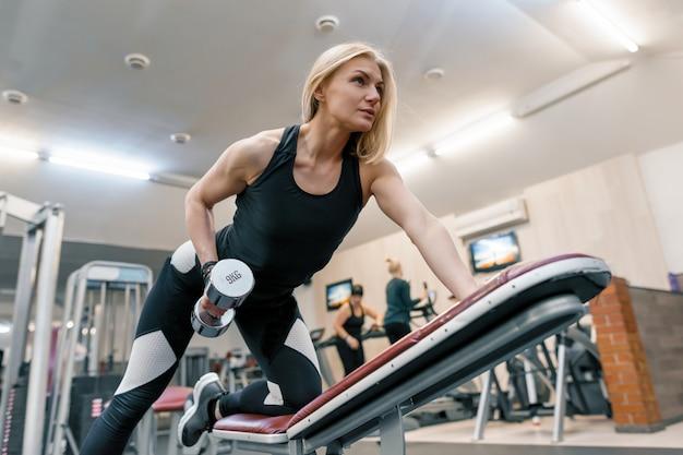 Молодая красивая белокурая женщина делает силовые упражнения