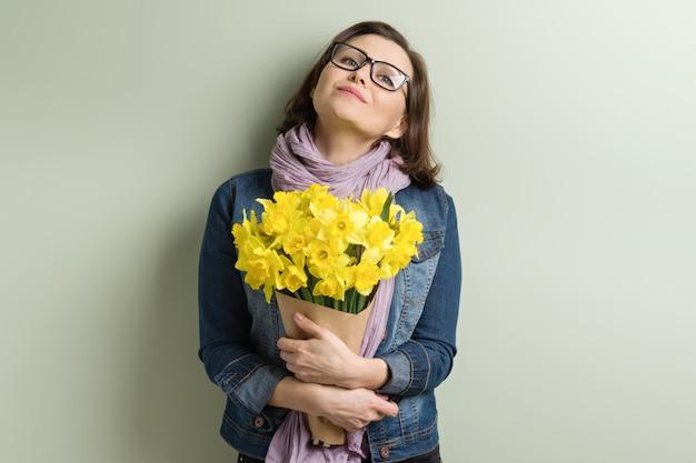 黄色の花の花束と幸せな中年の女性