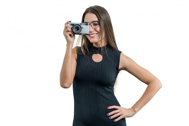 写真を撮る、彼女の手で写真のカメラを保持している黒いドレス眼鏡の若い笑顔の美しい女性