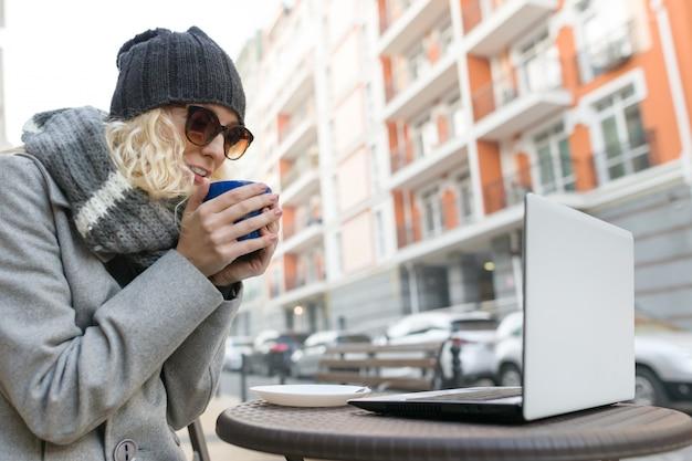 コンピューター、携帯電話のある屋外カフェで若い女性ブロガーフリーランサー。