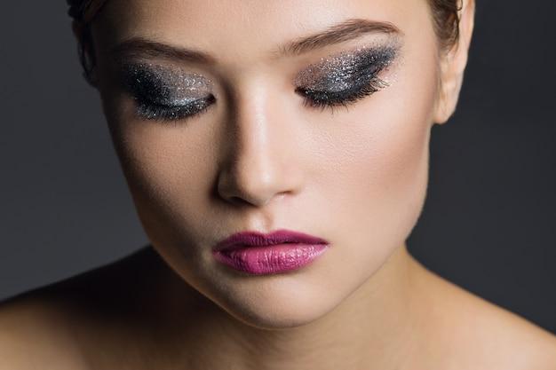 華やかなメイクアップを持つ若い女性の肖像画