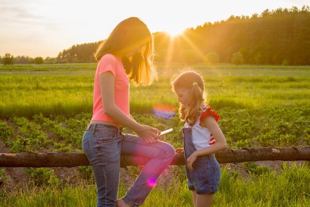 自然の中で子供たちはスマートフォンで遊ぶ。