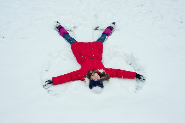 冬時間、雪、トップビューで楽しんで元気な女の子