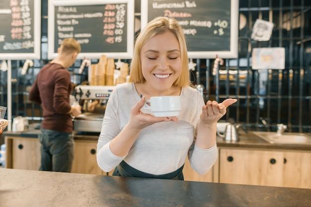 Молодая улыбающаяся бариста с чашкой кофе