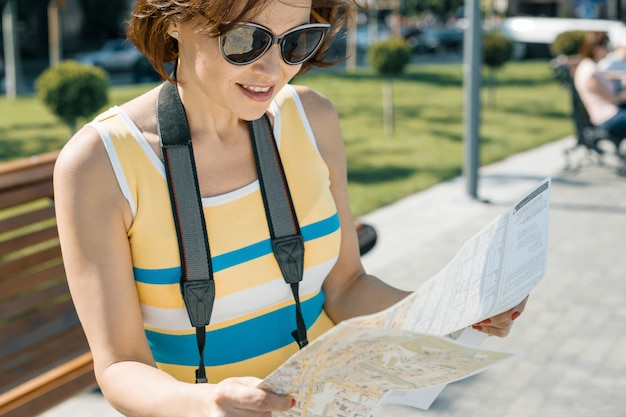 市内地図とカメラを持つ女性