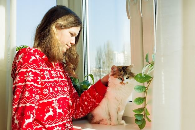 Молодая девушка в теплой пижаме с кошкой