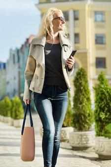 通りを歩いて若いブロンドの女性