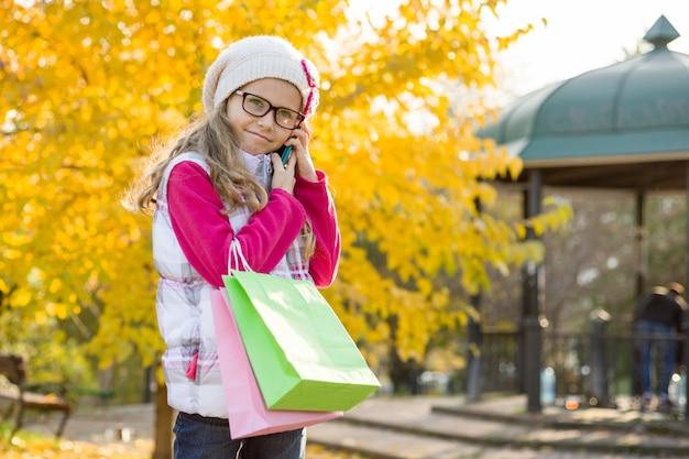 買い物袋と携帯電話を持つ子供の女の子