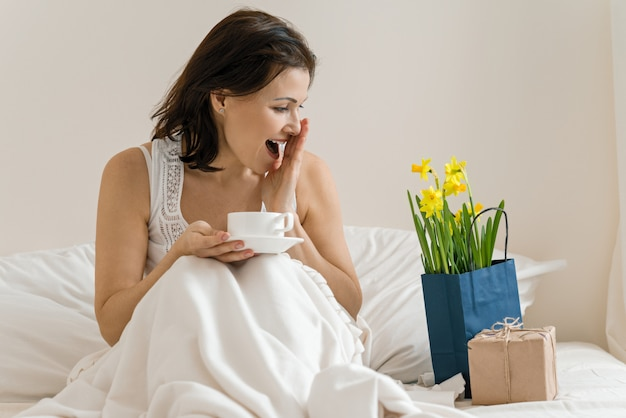 中年の女性は贈り物、花の花束、一杯のコーヒーと一緒にベッドで座っています。