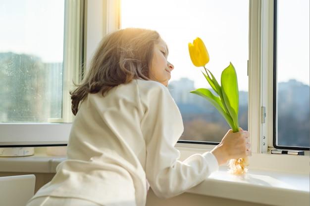 黄色のチューリップの花を持つ女児