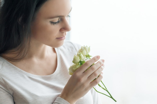 白いバラの花を持つ若いブルネットの女性