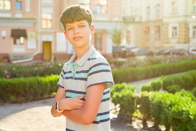組んだ腕を持つ屋外の少年