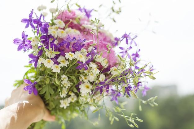 Женщина держит букет летних полевых цветов