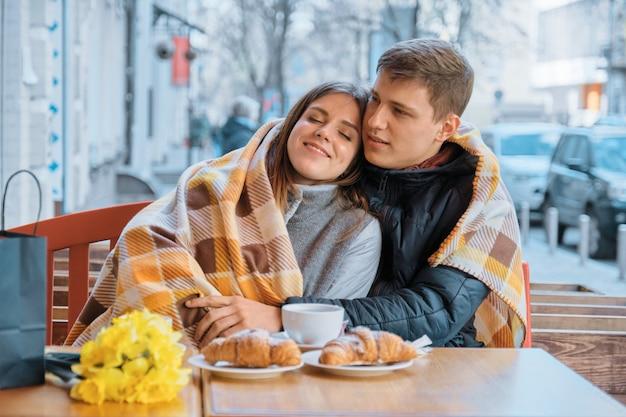 格子縞の下の屋外カフェで愛の若いカップル