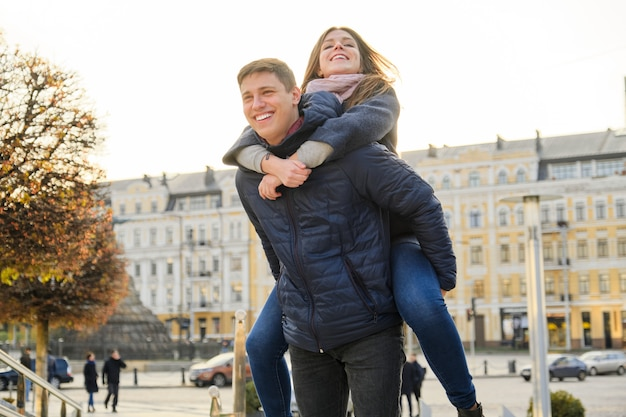 美しい学生のカップルが街で楽しんでいます。