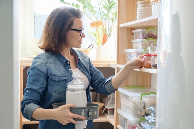 台所の収納キャビネットから食べ物を選ぶ中年女性