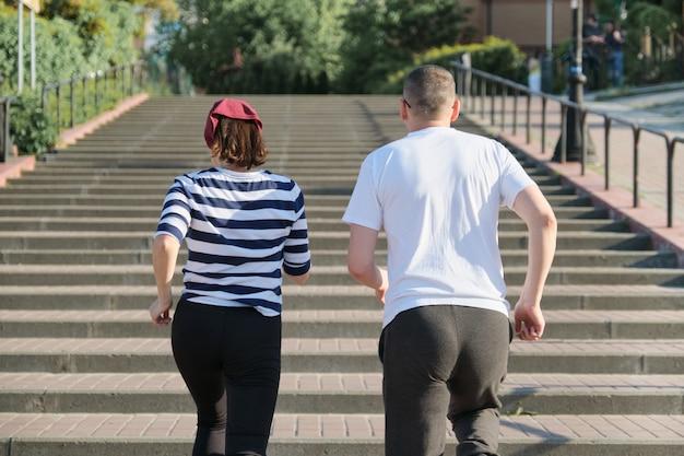 二階に走っている中年の男性と女性は後ろから見ます。