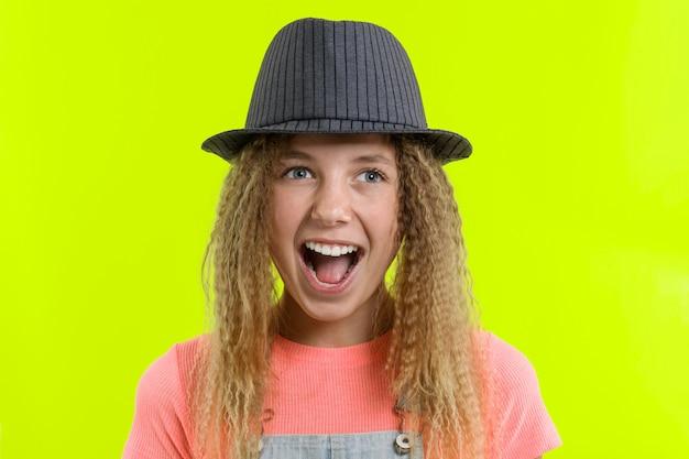 巻き毛の帽子と驚いた幸せな十代の少女
