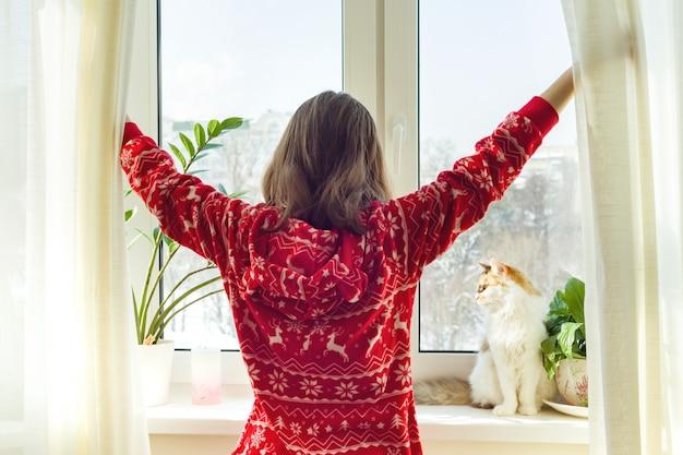 Молодая девушка в теплой пижаме зимой с кошкой