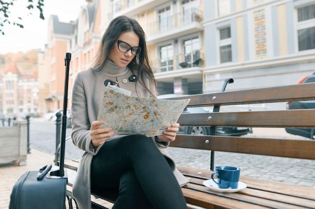 旅行スーツケースでベンチに座っている女性、市内地図を読む