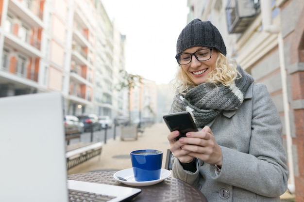 コンピューターと屋外カフェで若いビジネス女性