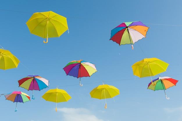 Много открытых разноцветных зонтиков на небе