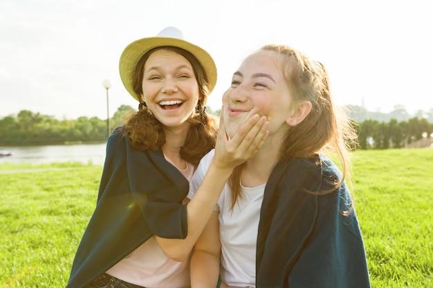 Молодые девушки с удовольствием сидят на зеленой траве газона