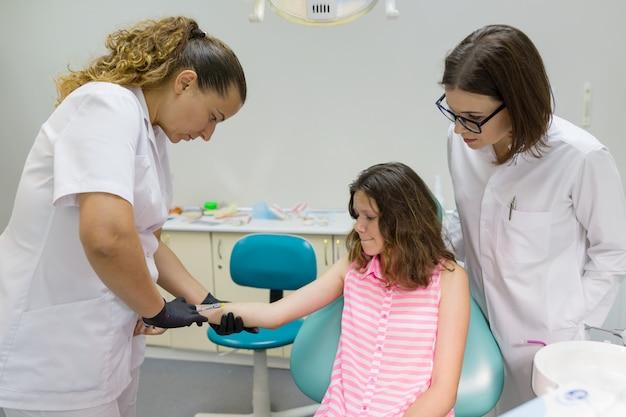 歯科医は手に注射し、反応を確認します
