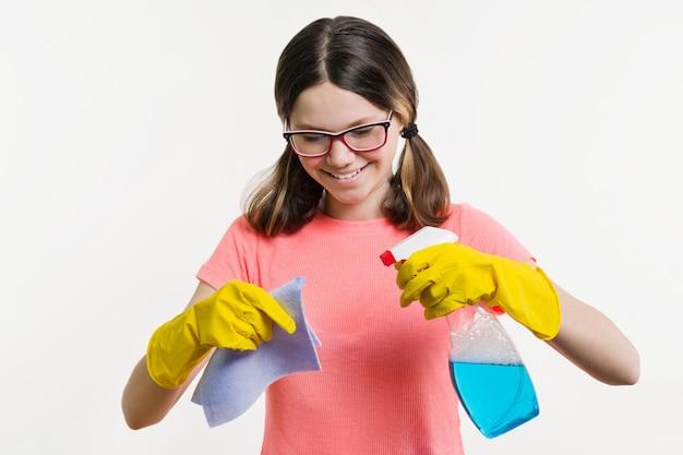 Девушка подросток в желтые перчатки с тряпкой и спрей моющего средства.