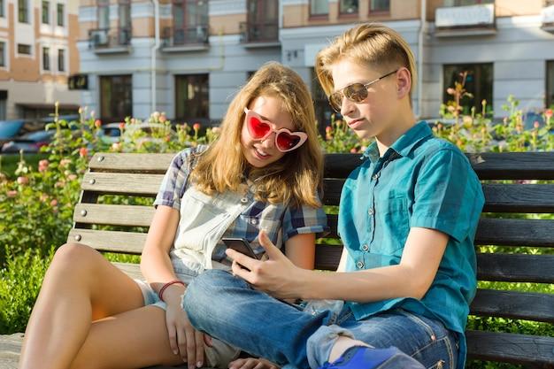Подростковые друзья девочка и мальчик сидят на скамейке