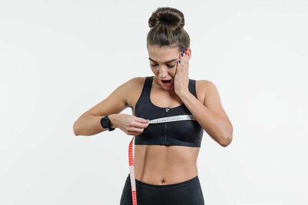 スポーツウェアの若い女性は、センチメートルのテープを保持して驚いています。