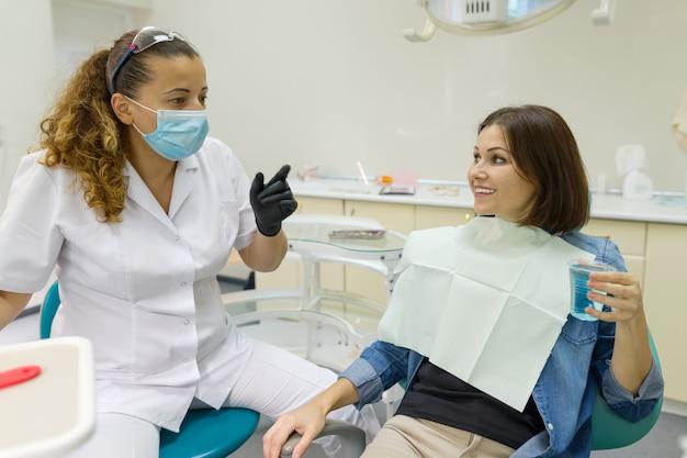 歯科医院で歯科医に話している女性患者